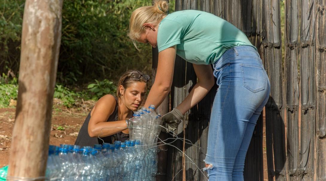 Volontärer bygger en vägg av plastflaskor som en del av plast och återvinningsinitiativet i Sri Lanka.
